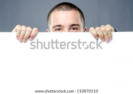 Pair of cheerful eyes  protrudes behind blank white board - stock photo