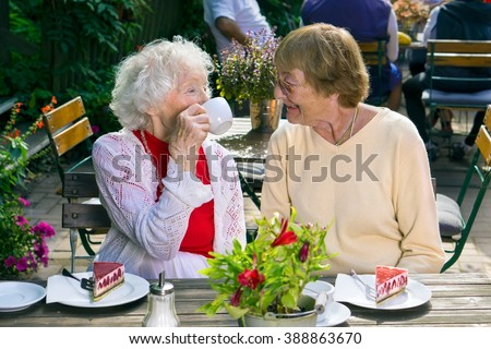 Pair of cheerful older ladies enjoying tea and cake in cafe while seated at wooden table outdoors. - stock photo