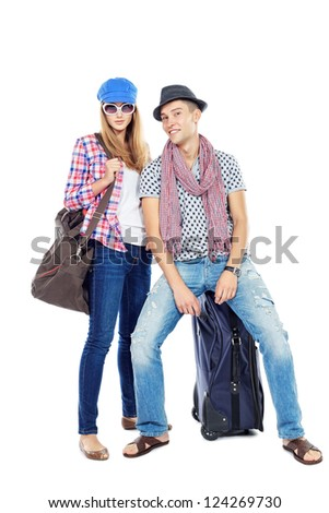 Pair of cheerful young people standing together with suitcases over white background. - stock photo