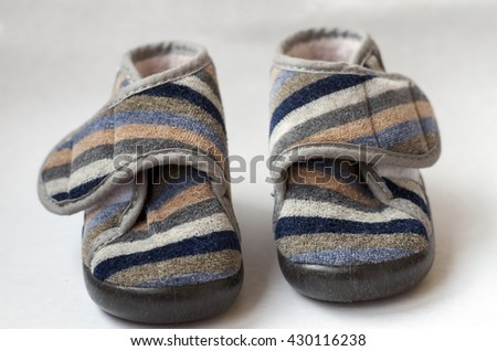 Pair of childs striped coloured shoes isolated on white background. Closeup/Childs colored shoes on a white background