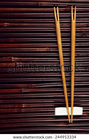 Pair of chopsticks on brown bamboo mat background - stock photo