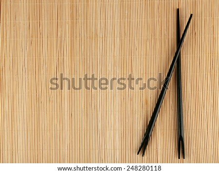 Pair of chopsticks on light bamboo mat background - stock photo