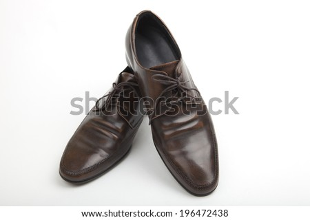 Pair of classic lace-up mens Polish brown leather shoes for formal wear or to wear to the office pointing towards the camera on a white background - stock photo