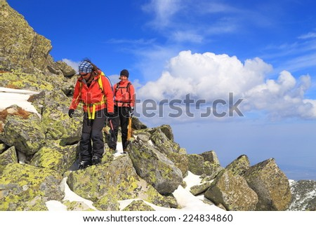 Pair of climbers crossing a rocky field on the mountain in winter - stock photo