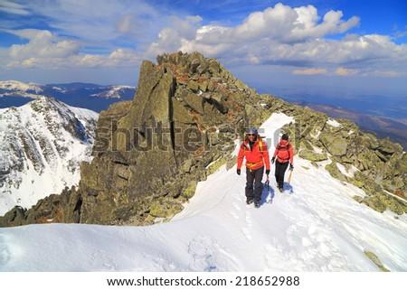Pair of climbers traversing a snow covered ridge on sunny mountain - stock photo