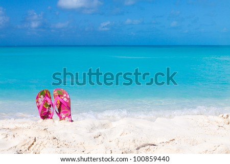 Pair of colored sandals on a white sand beach in front of the sea. The right place for relaxation and vacations - stock photo