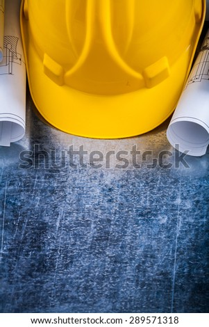 Pair of construction plans and hard hat on metallic background building and architecture concept. - stock photo