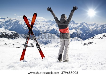 Pair of cross skis with woman skier, hands up - stock photo