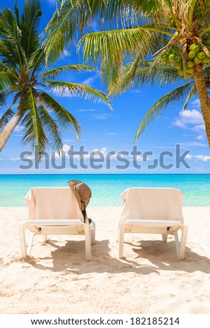 Pair of deck chairs between coconut palms on a tropical beach