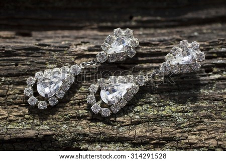 pair of diamond earrings on brown wooden texture - stock photo
