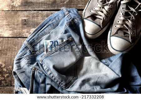 Pair of dirty jeans with twenty euro bill in the pocket thrown on floor with a pair of sneakers - stock photo