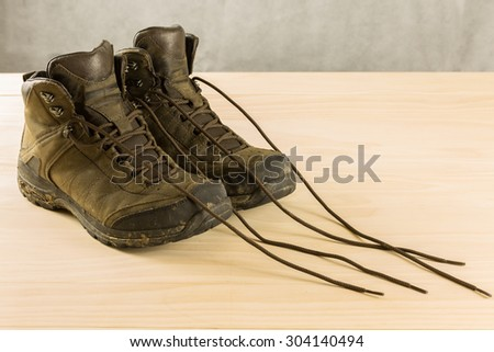 pair of dirty men hiking shoes on wood table - stock photo