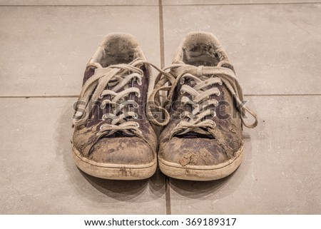 Pair of dirty shoes with mud on the floor