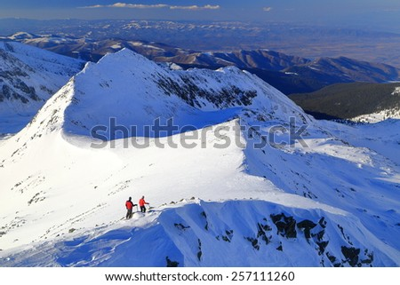 Pair of distant climbers on snow covered ridge in winter afternoon - stock photo