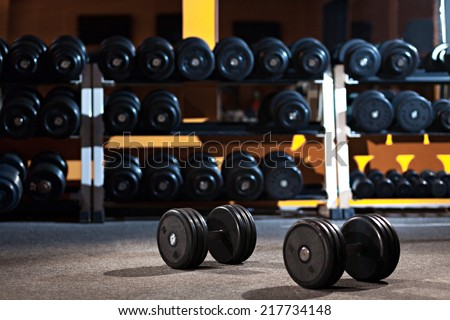 Pair of dumbbells on the floor of the gym are against row of dumbbells - stock photo