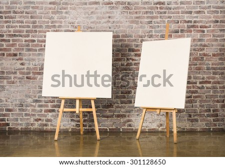 Pair of Easel with blank canvas on a brick wall background - stock photo