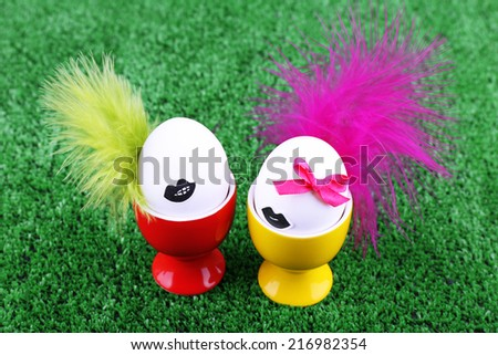 Pair of eggs in egg cups on green grass background - stock photo