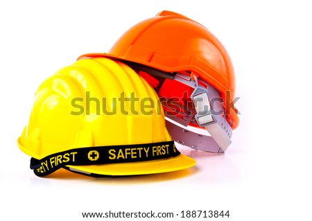 Pair of Engineer Worker Helmet two Orange and Yellow with SAFETY FIRST tag design concept isolated on white background. - stock photo
