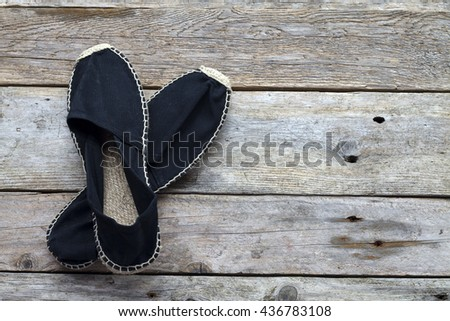 Pair of espadrilles on rustic wooden background