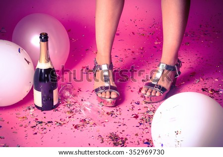 Pair of feet at a new years eve countdown party with confetti, champagne and balloons on the floor - stock photo