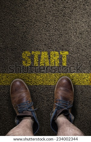 pair of feet on a tarmac road with yellow print of word start - stock photo