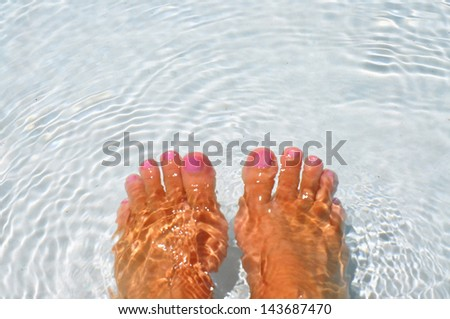 pair of feet soaking in water, room for your text - stock photo