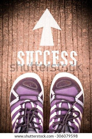 Pair of feet standing on rough cement floor with white print of word success