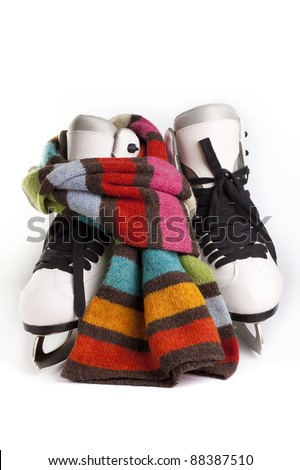 Pair of Figure Skates and a scarf on white background - stock photo
