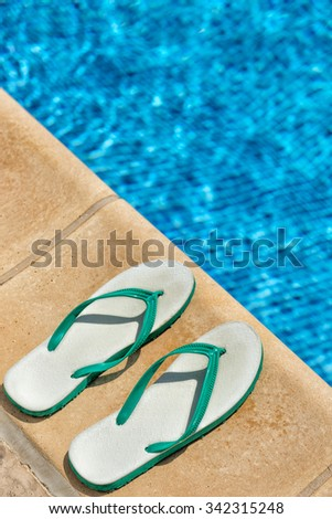 Pair of flip flop thongs and a towel on the side of a swimming pool - stock photo