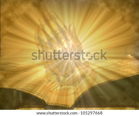 Pair of folded hands praying on golden lighted open bible - stock photo