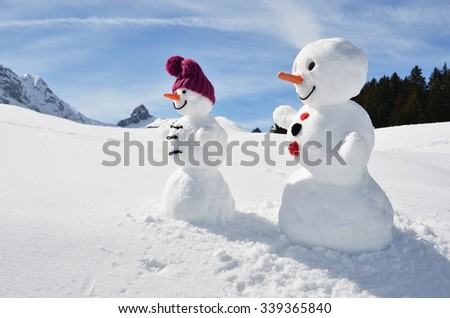 Pair of funny snowmen - stock photo