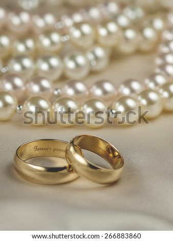 Pair of gold wedding rings with pearl background; focus on interior ring engraving: forever yours (Shallow DOF) - stock photo