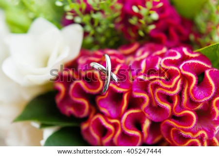 Pair of golden wedding rings inside a bouquetl. Bride's traditional symbolic accessory. Floral composition with red celosia flowers. - stock photo