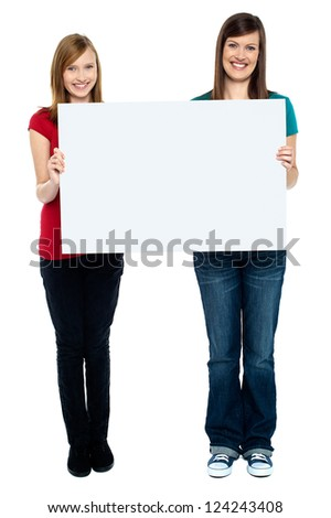 Pair of good looking women holding whiteboard. Full length portrait. - stock photo