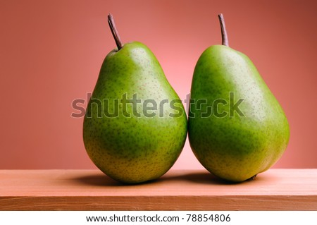 pair of green pears on pink background - stock photo