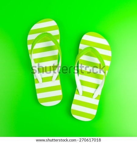 Pair of green striped flip flop on green background - stock photo