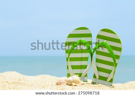 Pair of green striped sandal and seashell on the beach - stock photo