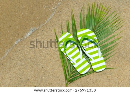 Pair of green striped sandal on the beach - stock photo
