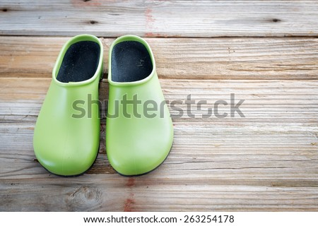 Pair of Green Waterproof Gardening Shoes on Wood Deck Surface with Copyspace - stock photo