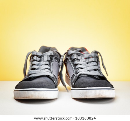 Pair of grey sneakers on colorful background.