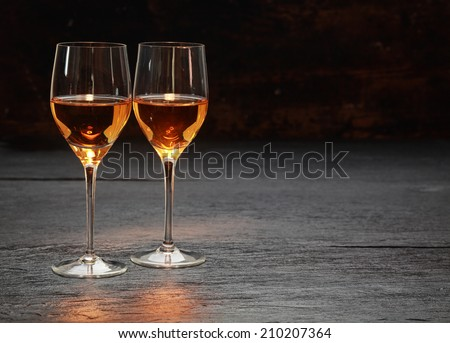 Pair of half-full half-empty wine glasses on stone surface - stock photo
