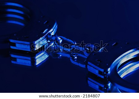 Pair of handcuffs in blue light - stock photo