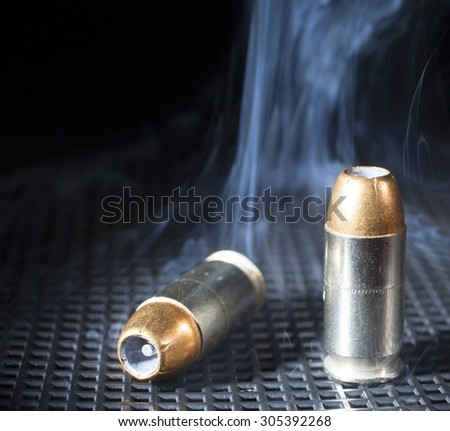 Pair of handgun cartridges that is surrounded by smoke - stock photo