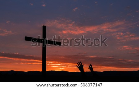 Pair of hands reach up to a black cross for salvation.