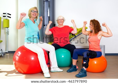 Pair of happy female patients and trainer flexing bicep muscles to show off their strength and confidence