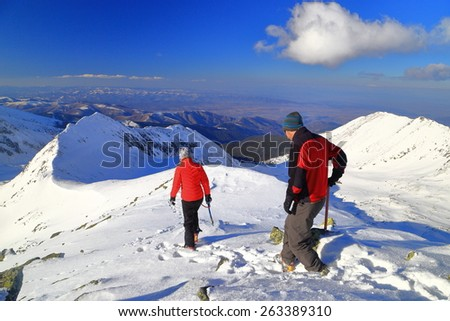 Pair of hikers descending sunny mountain in winter - stock photo