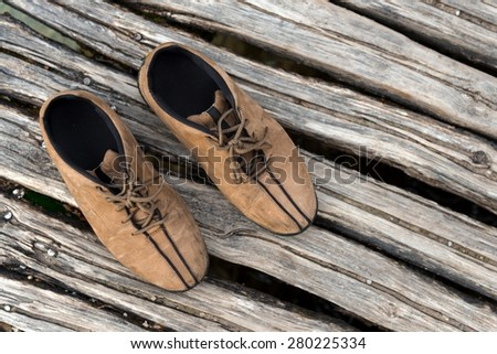 Pair of hiking shoes on wooden planks - stock photo