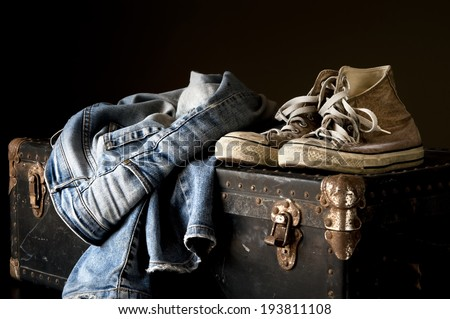 Pair of jeans and sneakers on a vintage suitcase - stock photo