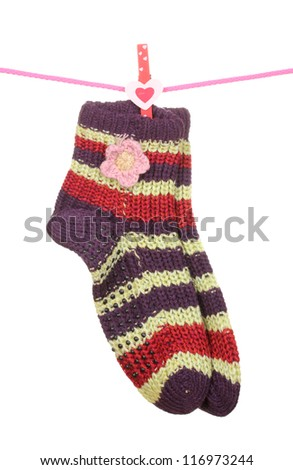 Pair of knit striped socks hanging on a rope isolated on white - stock photo