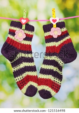 Pair of knit striped socks hanging to dry - stock photo
